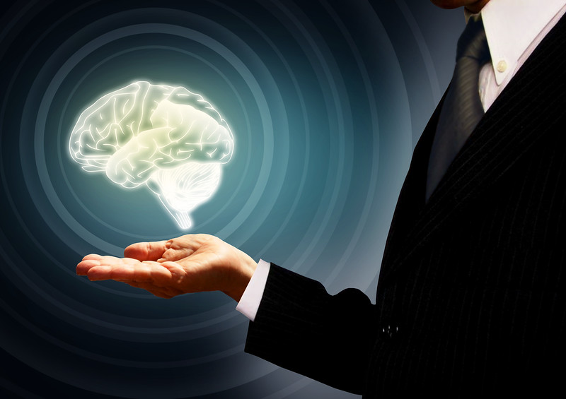 Businessman holding a brain in the palm - Skills concept - Concentric rings version