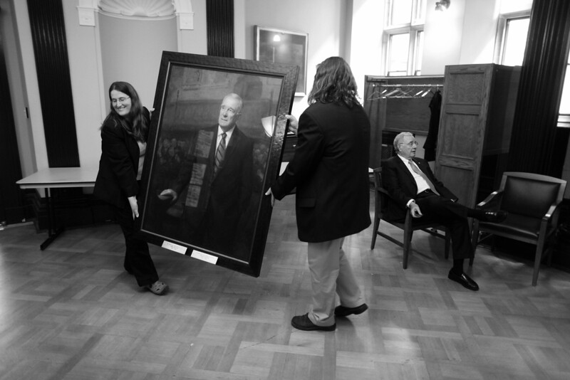 Former Prime Minister Paul Martin takes a seat while his official portrait is moved to be unveiling on Parliament Hill in Ottawa.