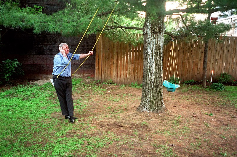 Paul Martin talks on the phone while sitting on a swing in Ottawa.