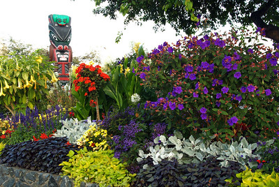 Totem pole with flowers on the corner of the harbor in front of the Empress Hotel and Parliament