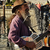 Victoria, B.C. busker and one man band, Dave Harris, plays his hillbilly train song for the crowds along the harbor sidewalk.