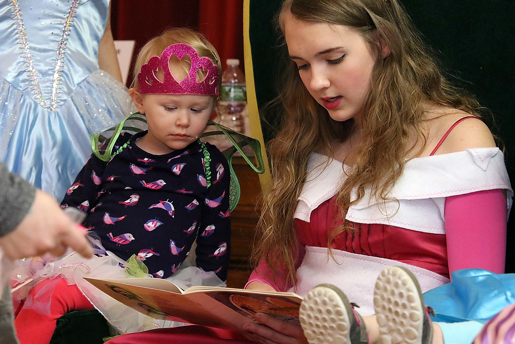 ". Thursday was ""Princess Day\"" at Leominster City Hall. Sylvia Radue, 2, listens to Sarah Whittier, 13, as she reads a book to the kids. She was playing Princess Aurora.  SENTINEL & ENTERPRISE/JOHN LOVE"