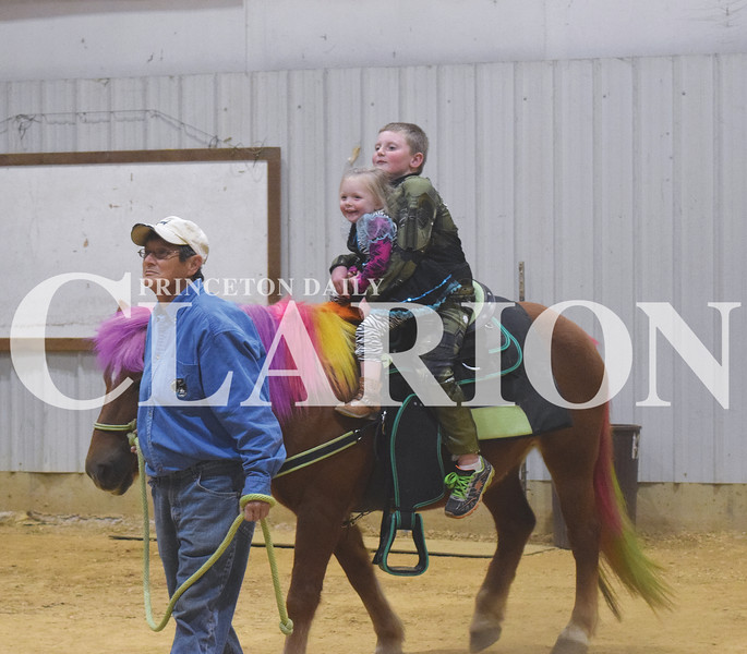 Walynn Taylor, 7, and Lillian Steven, 3, ride a horse at the Princeton Daily Clarion's Harvest Festival Thursday night at Gibson County Fairgrounds Pavilion in Princeton.
