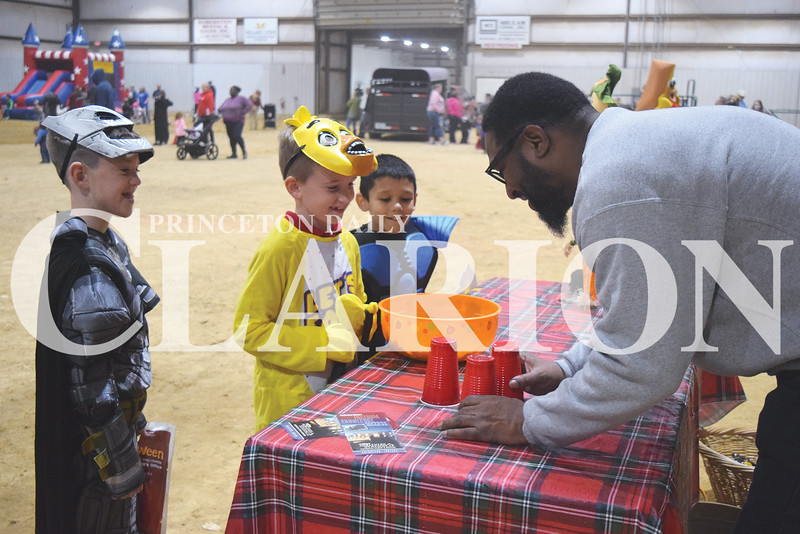 Ethan Queen (Batman), 8, Conner Stewart (bird), and Bryley Morrow (blue ninja), 6, laugh as Tyson Sim asks them which cup has a ball underneath it at the Lyles Station booth at the Harvest Festival.