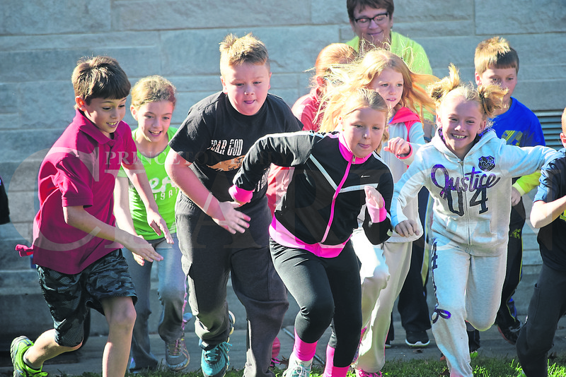 """Students from St. Joseph Catholic School jogged around the school for about 20 minutes Monday afternoon as part of the annual Red Ribbon Week campaign. Monday's theme was """"run away from drugs."""""""