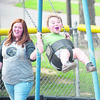 Daily Clarion/John Roark<br /> A swinging good time!<br /> Elliot Heidt, 3, shares a laughwith his mother, Ashley Harmon (left) during a swing session at Lions' Kiddieland Park in Princeton. Elliot's infant sister Lucy Heidt, was also present but not pictured.
