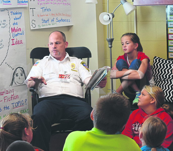 """Princeton Fire Chief Mike Pflug reads from the book """"Scaredy Squirrel"""" Thursday afternoon at Princeton Community Intermediate School. Several community members read to students as part of the """"Reading Tigers"""" program launch."""