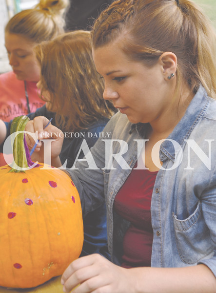 Daily Clarion/Andrea Howe<br /> Samantha Gharst paints purple polka-dots on her pumpkin during one of the activities at Lyles Station's New Beginnings Celebration Saturday afternoon.