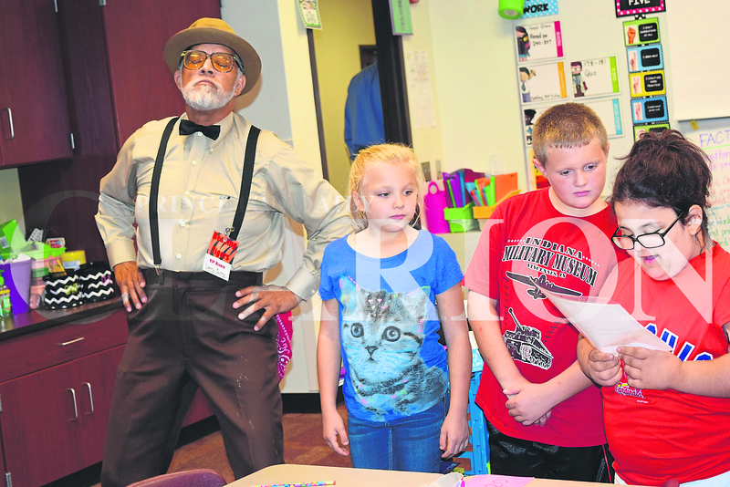 "From left, volunteer storyteller Larry Curry portrays his character ""Mr. Roundtree"" as Jaeley Payne, Phoenix Devine and Ella Hughes read to the class during Princeton Community Intermediate School's ""Reading Tiger"" launch on Thursday."
