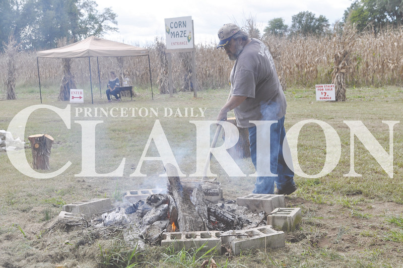 Daily Clarion/Andrea Howe<br /> Gary Schmidt stirs the coals in a campfire ready for hot dog or s'mores roasting at the Lyles Station New Beginnings Celebration and corn maze. The maze opened saturday and will be open through October on weekends.
