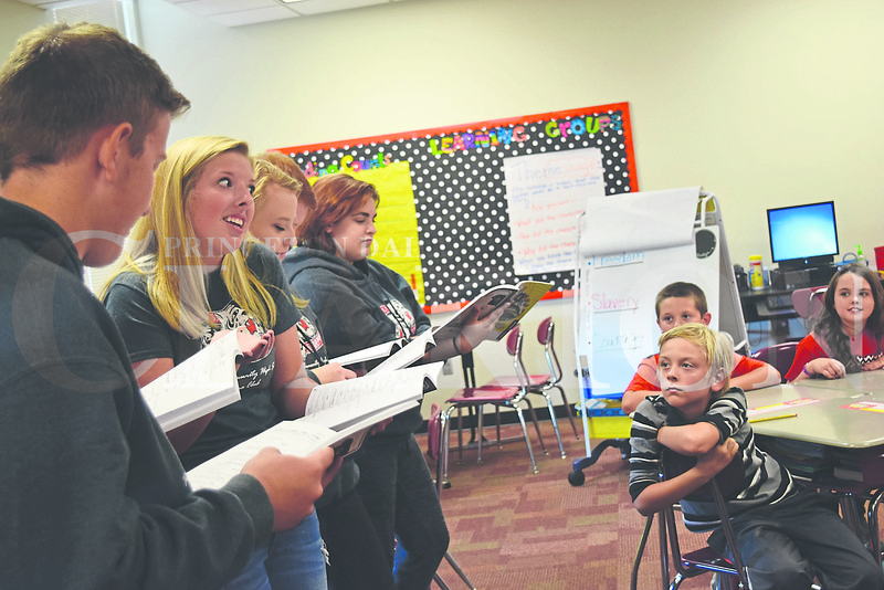 """Zachariah White (right) listens on as members of the Princeton Community High School Drama club read during Thursday's """"Reading Tigers"""" launch at Princeton Community Intermediate School."""