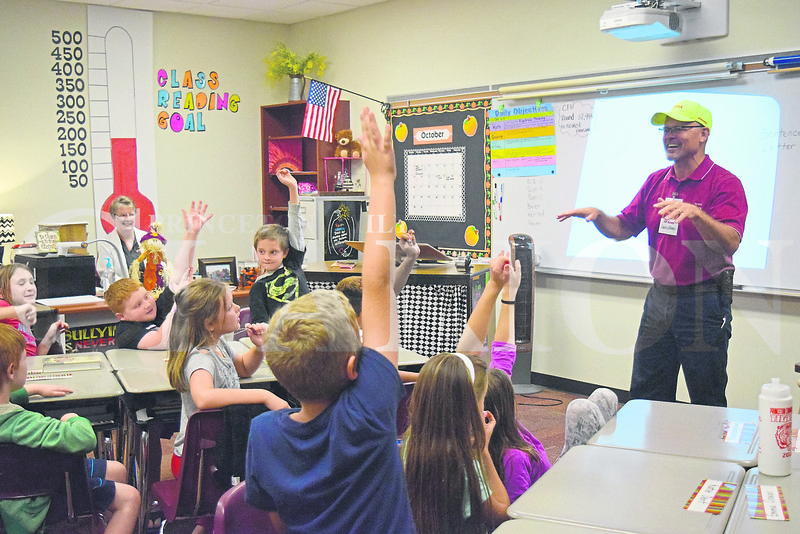 """Volunteer reader Charlie Wonnell with Toyota Motor Manufacturing Indiana Human Resources Department asks students how long they have been reading  during Princeton Community Intermediate School's """"Reading Tigers"""" launch Thursday afternoon."""
