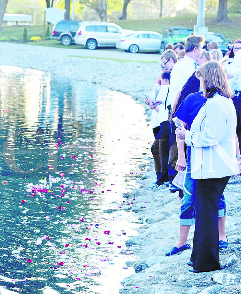 """Daily Clarion/John Roark<br /> Participants during Thursday's fourth annual Flowers on the Lake event watch the petals collect at Lafayette Park in Princeton. The event highlights awareness of National Domestic Volence Awareness Month, as well as kicks off October's Purple Light Nights campaign in Gibson County. Several speakers took part in the ceremony, while Princeton Community High School's choir performed a rendition of John Lennon's """"Imagine."""""""