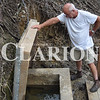 Phil Scott looks into Dripping Springs, a 4-by-4 foot well he and Kevin Robinson uncovered with the help of a Track Hoe.