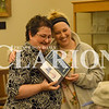 Rachel Graber Akpotu/Daily Clarion Celebrating 100 years... Fort Branch Public Library Director Sabrina Frederick revealed the new library logo  with contest winner Justine Mayer Tuesday evening. Library Board of Trustees sorted sorted through  submitted logo drawings from seven different people as part of the 100 year anniversary of the library. Mayer received a $100 prize for the winning design.  Runners up included Jackson Campbell and Clint Johnson.