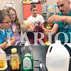 Daily Clarion/Andrea Howe<br /> Princeton Community Middle School STEM camp students watch science teacher Jim Maglis pour honey into a tube after corn syrup, followed by dish soap, water, cooking oil and alcohol, to test their hypothesis regarding which liquids were heavier. Pictured are Gavin Phillips, Layla Howell, Quinn Bush and Jace Jenkins. The students predicted that the honey would be the heaviest liquid.