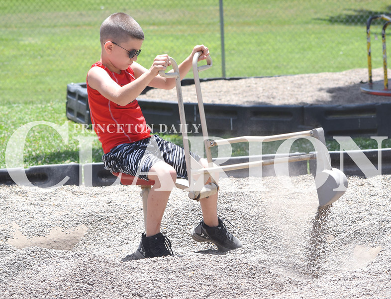 Quiche Matchen/ Daily Clarion<br /> Bently Ray, 7, picks up and drops rocks with playground equipment at the Lions Kiddie Land Park in Princeton Wednesday evening.