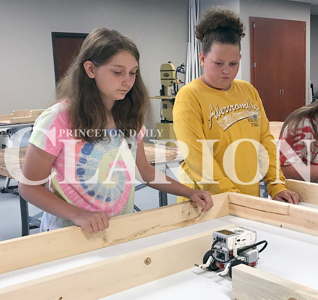 Daily Clarion/Andrea Howe<br /> Allie Kohlhaus and Chloe Smith watch their robot maneuver through a maze according to the computer programmed commands they created at Thursday morning's STEM camp at Princeton Community Middle School.