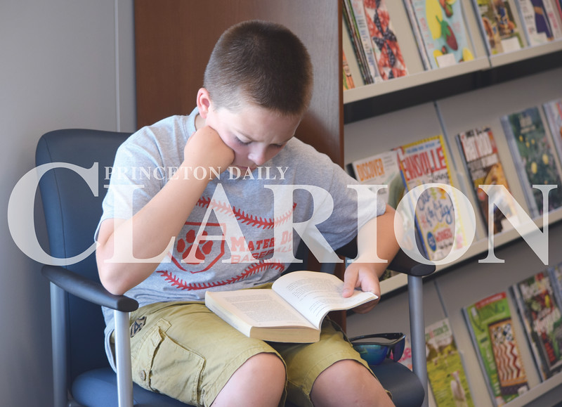 """Quiche Matchen/ Daily Clarion<br /> Jack Bonham, 11, reads """"Stormbreaker"""" while his siblings listen to Evansville Otters baseball players ready to them at the Haubstadt Library Tuesday morning."""