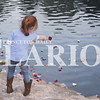 Quiche Matchen/ Daily Clarion<br /> Aislyn Leonard, 5, throws flower petals into the lake at Lafayette Park to remember domestic violence victims at the fifth annual Flowers on the Lake event. According to the program, there were 64 domestic violence victims, 515 domestic violence calls to 911 and 140 victims who filed restraining orders in Gibson County in 2016.