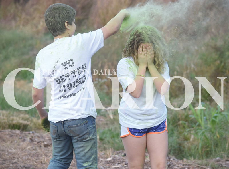 Quiche Matchen/ Daily Clarion<br /> Kyle Fravel pours green color run powder on Kendal Gomez as she makes her first lap of the 5K color fun run/walk Saturday morning at Hopkins Family Park in Francisco.