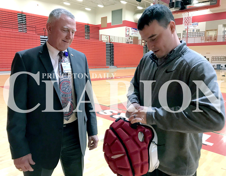 Daily Clarion/Andrea Howe<br /> Gibson General Hospital CEO Emmett Schuster watches Princeton Community High School head football coach Jared Maners remove the Guardian Cap cover from a football helmet.