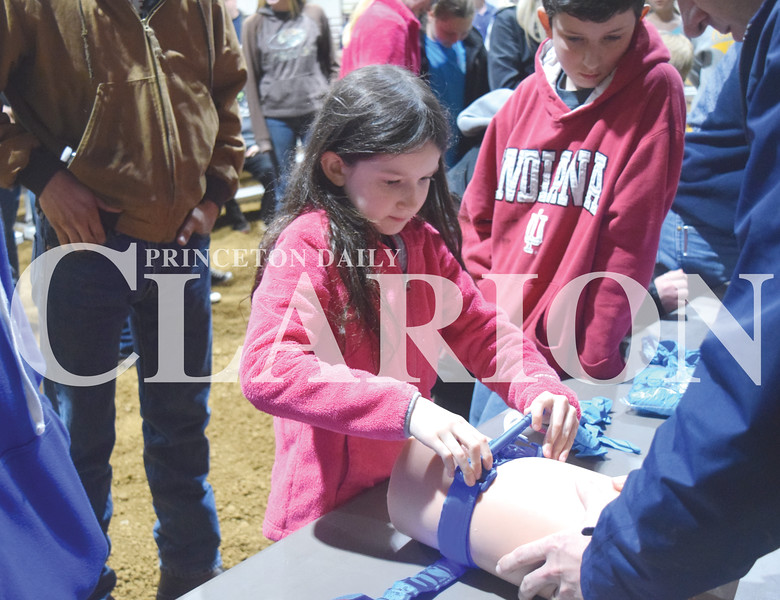 Quiche Matchen/ Daily Clarion <br /> Lydia Munro, 8, was the first volunteer to apply and tie a tourniquet on a dummy Tuesday evening at the Gibson County Fairgrounds Pavilion. Attendees also learned how to pack an open wound.