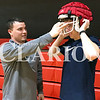 Daily Clarion/Andrea Howe<br /> Princeton Community High School varsity football coach Jared Maners helps Will Huff try on a football helmet equipped with a new Guardian Cap soft-shell helmet cover. The covers were purchased by Princeton Football Boosters with help from a $5,000 donation from Gibson General Hospital.
