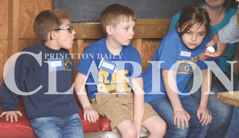 Quiche Matchen/ Daily Clarion <br /> Leyton Schmitt, Evan Weisheit and Aubrey Sollman, all St. James Catholic School first graders, listen to Stanley Madison talk about different beans at the work and play field trip Friday afternoon at Lyles Station.