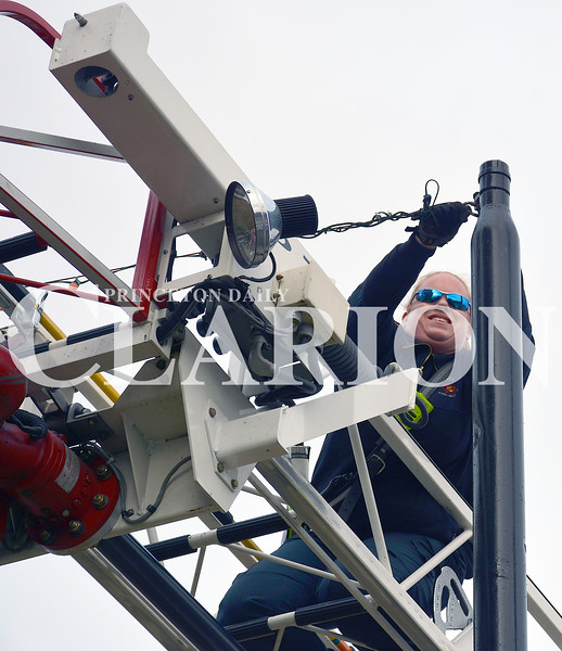 Daily Clarion/Andrea Howe <br /> Princeton Fire Territory firefighter Beth Mincey uses the aerial ladder truck to attach a strand of Christmas lights to an anchor pole on the Gibson County Courthouse lawn Sunday afternoon.
