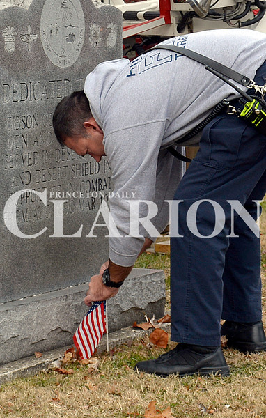 Daily Clarion/Andrea Howe <br /> Firefighter Tracy Krieg stops Sunday afternoon to adjust a flag planted at the memorial on the Gibson County Courthouse lawn dedicatd to veterans of Operation Storm and Desert Shield.
