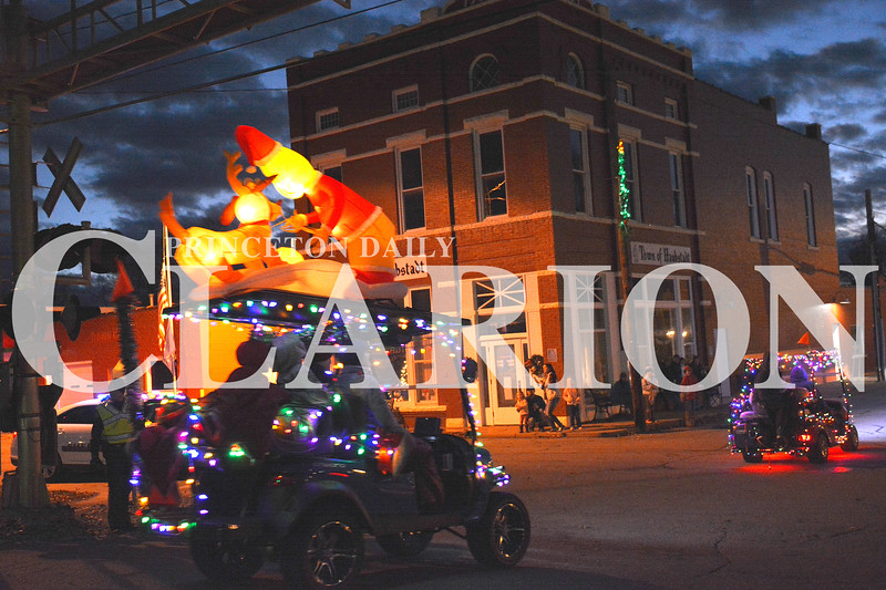Daily Clarion/Andrea Howe<br /> Santa nudges Rudolph along the roof of a festive golf cart, one of more than 50 entries in Haubstadt Chamber of Commerce's annual Christmas golf cart parade Sunday night through Haubstadt. The parade entries traveled the neighborhoods and downtown Haubstadt en route to the old gym, where a tree-lighting ceremony took place.