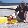 Quiche Matchen/ Daily Clarion <br /> Zane Beard, Gibson Southern High School senior, paints a traffic island near Owensville Town Hall Tuesday morning, during the annual Youth Day of Caring. Free lunches were provided for all participants.