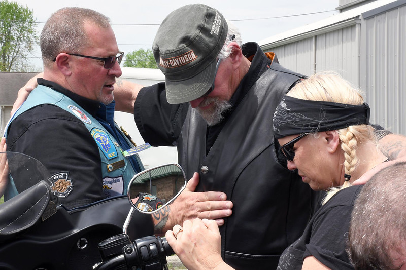 Daily Clarion/Andrea Howe<br /> Dan Walls, chaplain for the Blue Knights motorcycle group, prays with Brian and Catherine Rexing of Evansville, who rode to Princeton for Bike Sunday at Oasis Assembly of God.