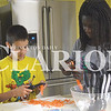 Nathan Schleter, 11, and Mary Amsbury, 14, cut up fresh carrots before boiling them Wednesday morning at the Gibson County Fairgrounds Activities Building. The food science frenzy was hosted by the Gibson County Purdue Extension office for children in grades 6-8.