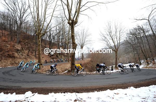 Saxo Bank is still leading the peloton as it descends through a frigid-looking forest...