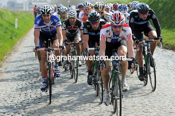 Sky starts to show itself with Arvesen leading the peloton along the cobblestones near Volkegemberg...