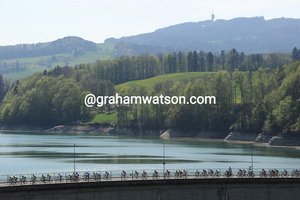 The peloton is strung out as it crosses a dam across Lac Gruyere...