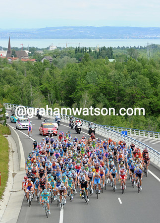The peloton is about to start racing as it pulls away from the Lake of Geneva...