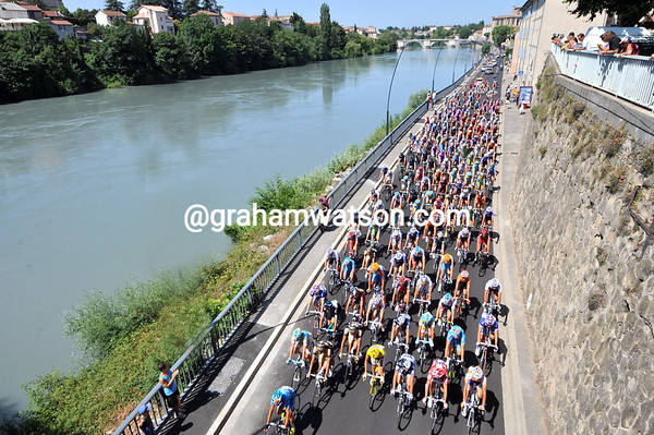The peloton enjoys its neutralised zone along the banks of the Isere river at Romans...