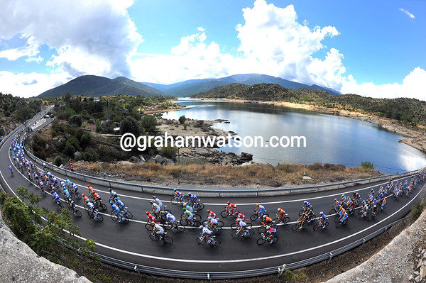 The peloton is still stretched out as it crosses the Embalse El Burguill halfway through the long stage...