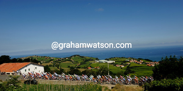 The peloton climbs the Alto del Garate against a peaceful backdrop of the Bay of Biscay...
