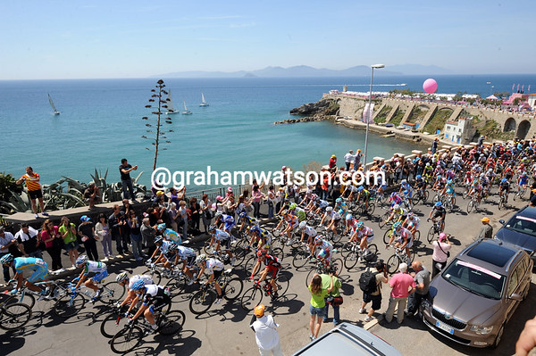 A happier peloton leaves Piombino with views across to the Isle of Elba...