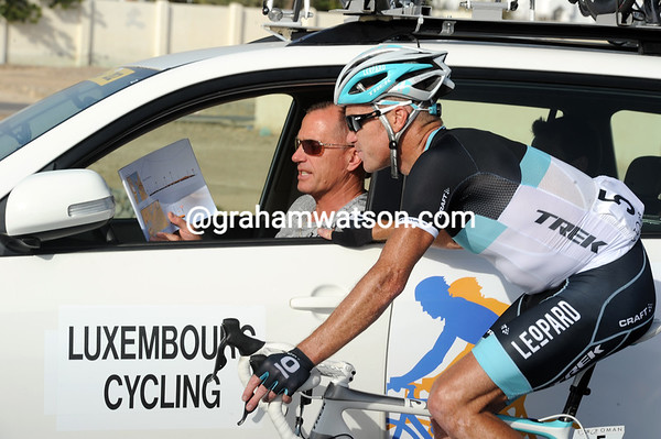 Stuart O'Grady gets called back to his team car to study the race manual, under the guidance of Kim Andersen...