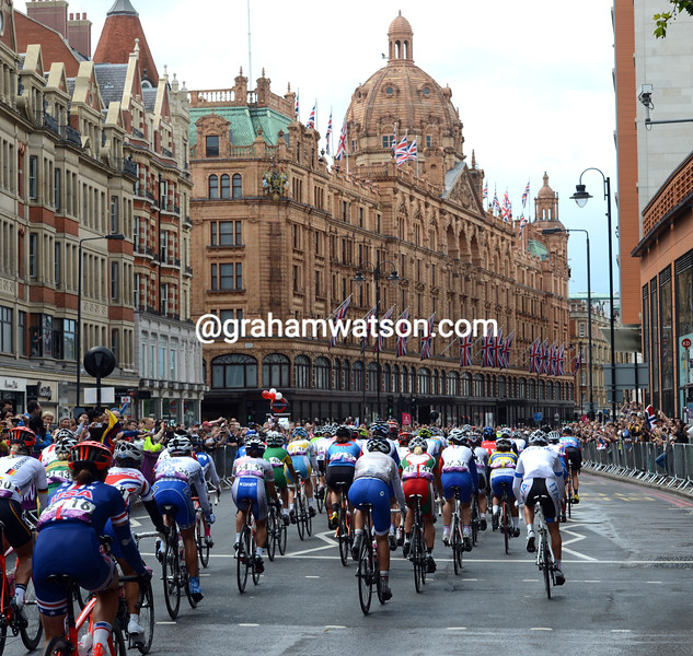 The peloton is still intact as it passes Harrods in Knightsbridge a few kilometres into the day
