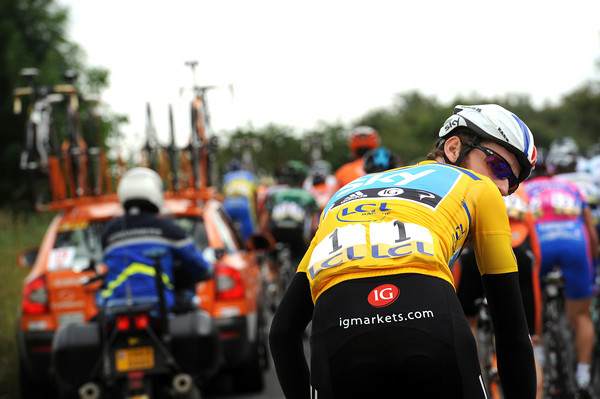 Bradley Wiggins looks back for his team car to fetch his own rain-jacket...