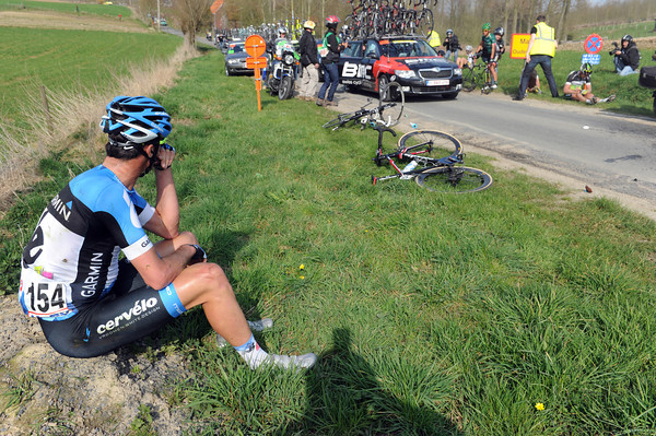 A thoughtful David Millar nurses a broken collar-bone as he waits for the ambulance...