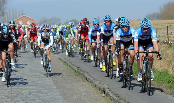 Team Garmin takes the smooth road alongside some cobbles near Poperinge...