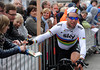 Looking like a modern-day Tom Simpson, Mark Cavendish signs a fan's autograph on the way to the start...