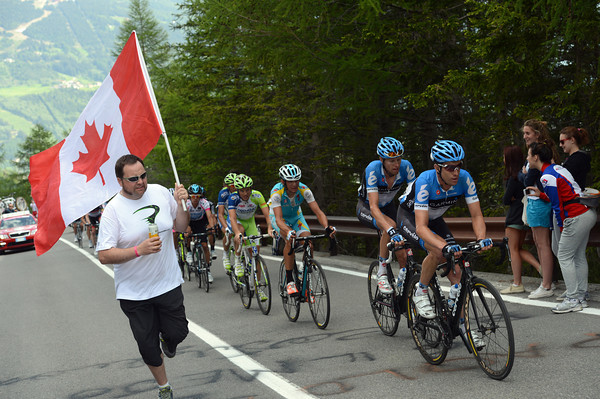 A Canadian fan runs alongside Vande Velde and Hesjedal as the chasing group begins to shrink...